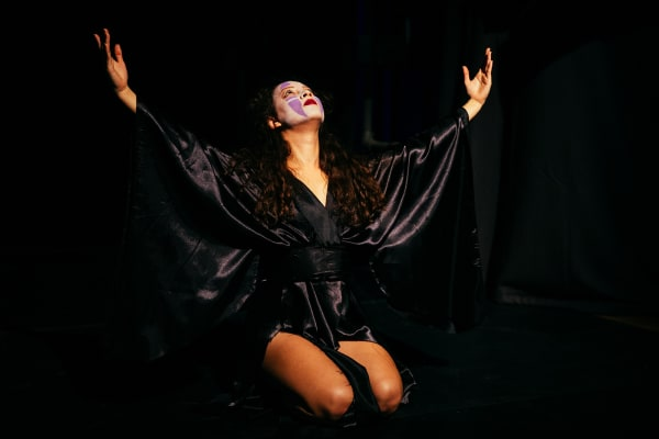 Acting performance on stage, girl on her knees with hands wide open