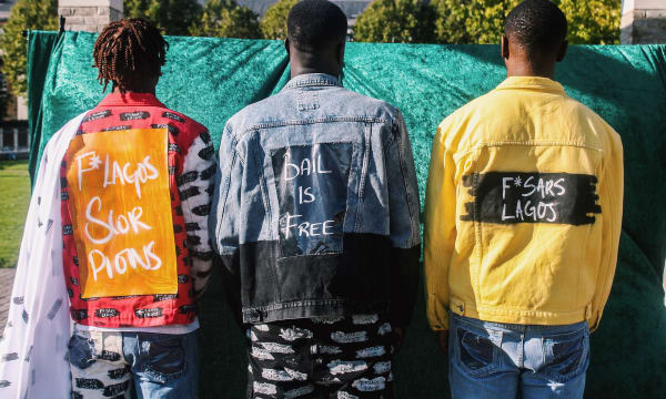 Three men with jackets with 'Bail is free' written on back