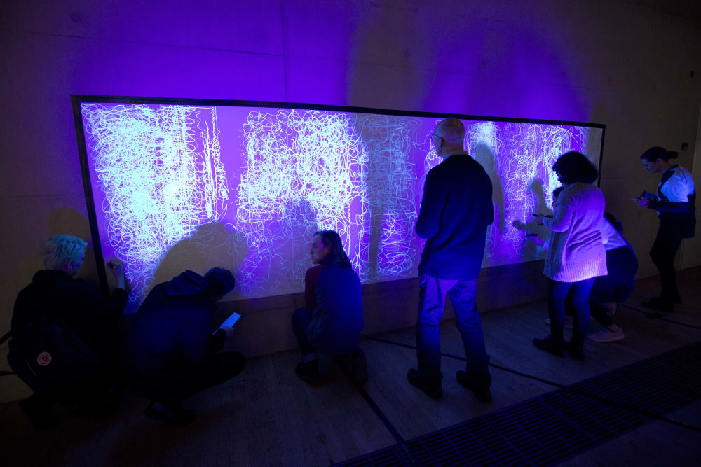 People standing in front of a screen in a purple-lit room
