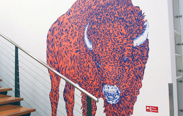 Graphic of a red and blue drawing of a buffalo on a white wall