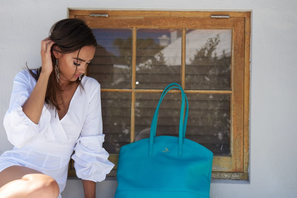 A model poses with an aqua coloured bag, in front of a window