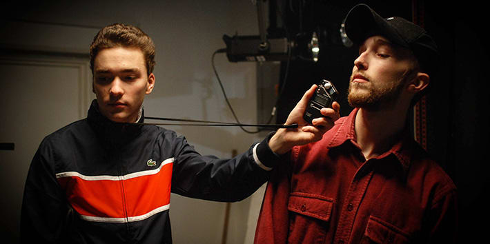Two students with a light meter in one of the studios
