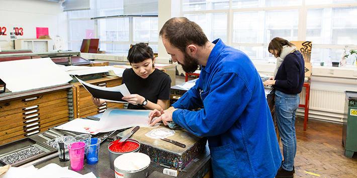 A technician assisting a student with ink mixing in the Letterpress workshop.