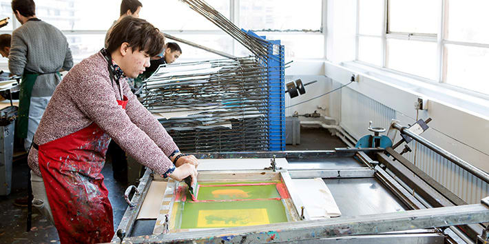 A student in the process of screen printing.