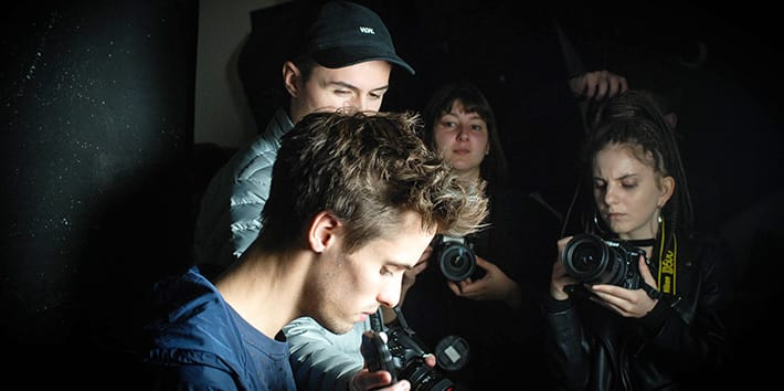 A group of students operating cameras in a darkened studio.