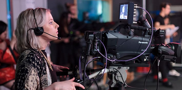 A student operating a video camera in the TV Studio.