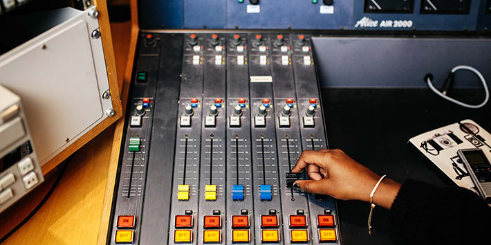 Student controlling slider on mixing board in an audio studio.