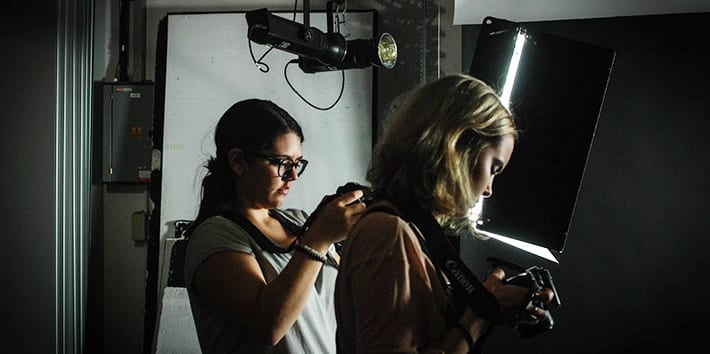 Two students operating cameras in one of the photography studios.