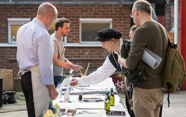 Photo of a group of people at a table outside using paintbrushes