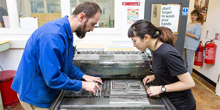 A technician assisting a student with typesetting in the Letterpress workshop.