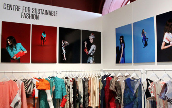 Racks of clothes under large photos at Centre for Sustainable Fashion