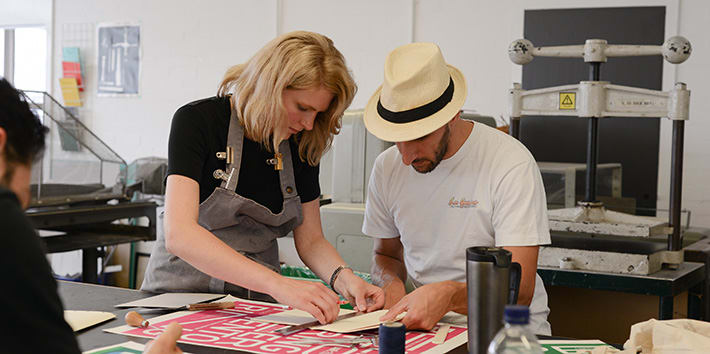 A technician working with a student in the Book Arts workshop.