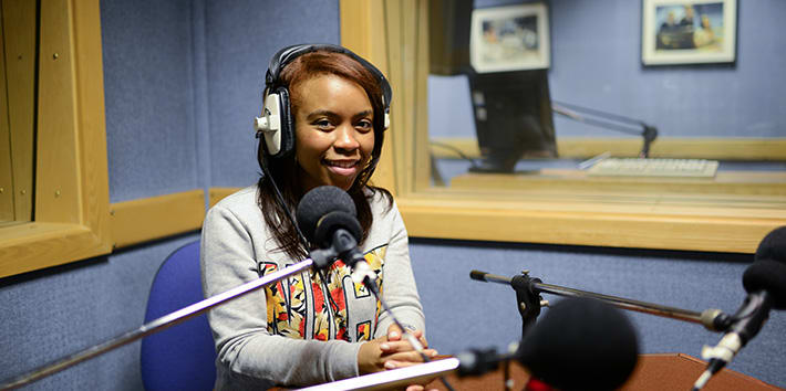 A Journalism student recording dialogue in the audio studio.