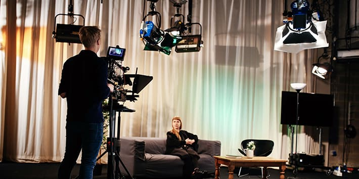 A student operating a video camera, on set, in the TV Studio.