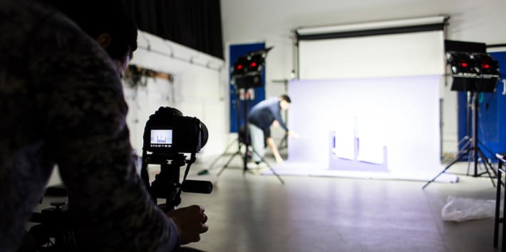 A student taking a photo in a Design Block Photography Studio.