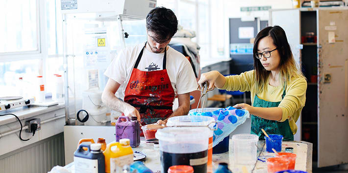 Two students preparing specialist dyes for textile printing.