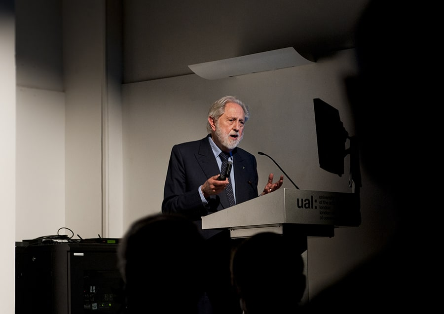 Lord Puttnam speaks on a podium in a lecture theatre at LCC