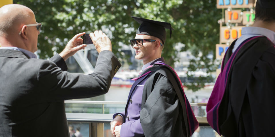 Graduate having their photo taken by a family member.