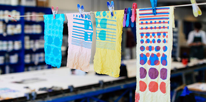 A series of student experiments with textile print hanging to dry.