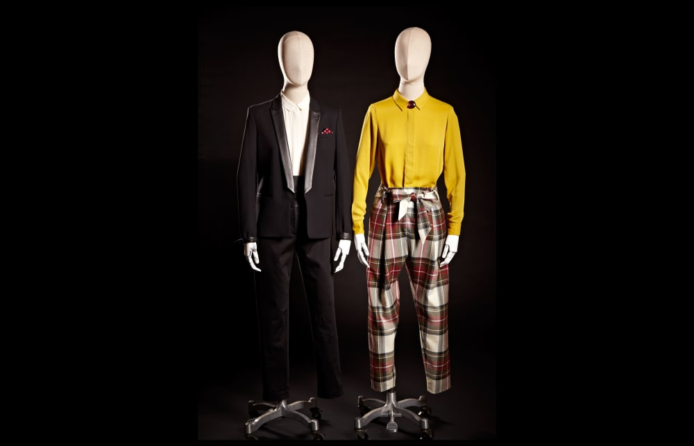 Two mannequins wearing androgynous clothing - one a tuxedo, the other tartan trousers and a mustard shirt.