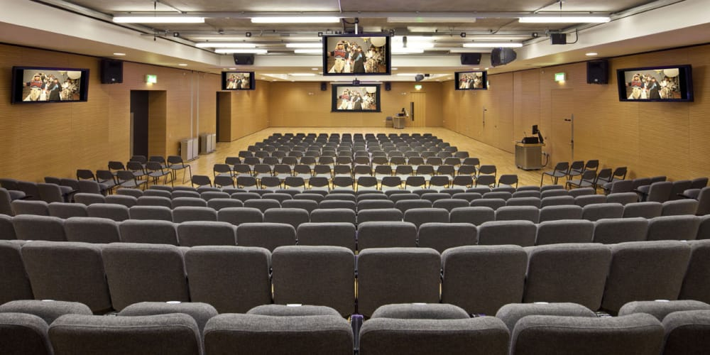 A row of grey seats in an empty lecture theatre