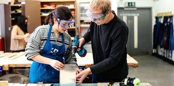 A technician assisting a student with a hand drill in the 3D Workshop.