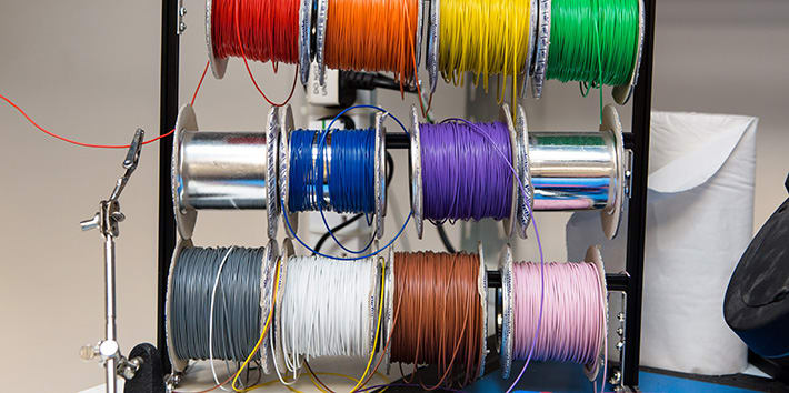 A rack of multi-coloured wire rolls.