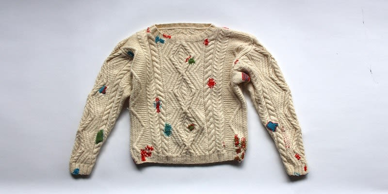 A beige/white woolen jumper with colourful splodges all over