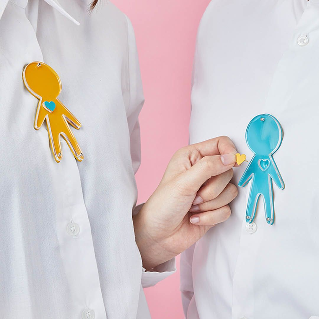 Figures wearing yellow and blue people-shaped brooches
