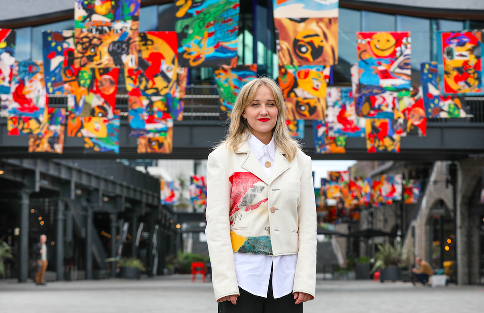 Image of Bethany Williams in cream two piece with decorative patterns on waistcoat, with multicoloured flags in the background.