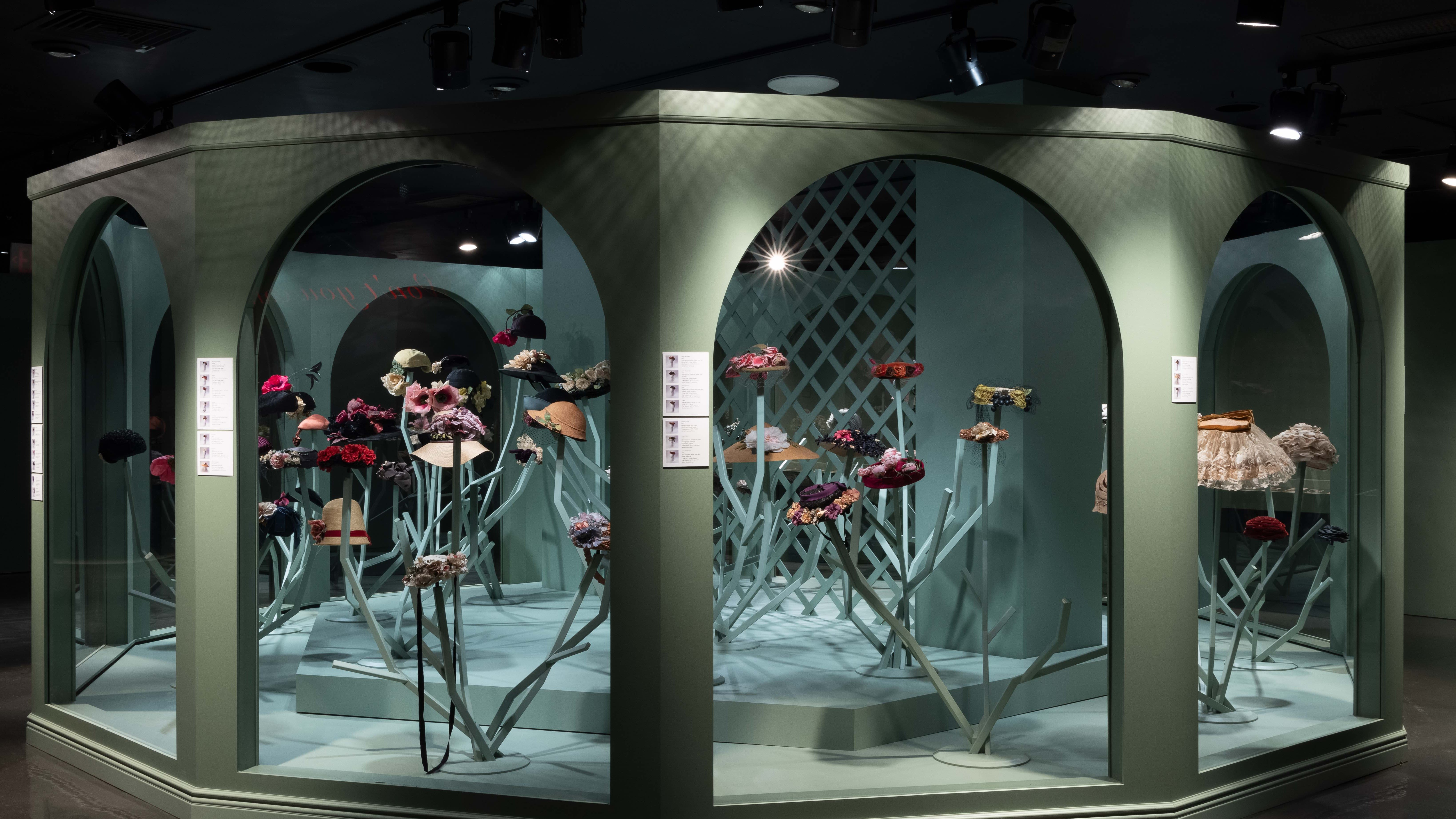 Brances of roses enclosed in a pentagonal glass case, located in a dark room with electronic teal-coloured lighting.