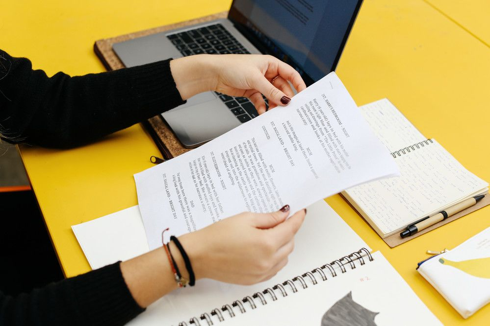 Close up of a woman's hands holding papers against a yellow desk with a laptop and notebooks