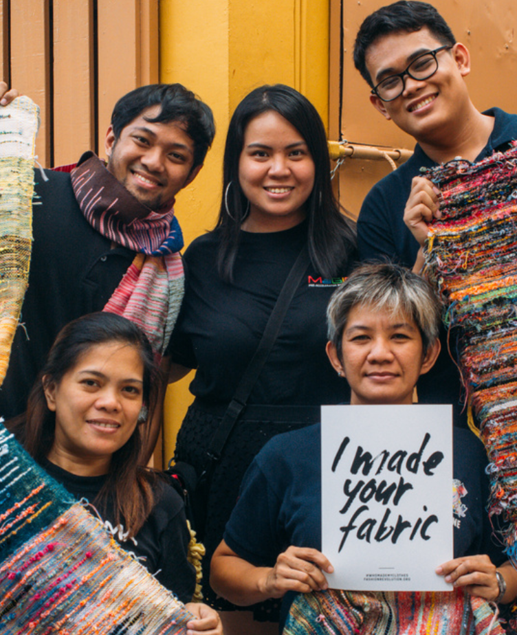 5 garment workers posing, with one holding a sign in the bottom right that reads
