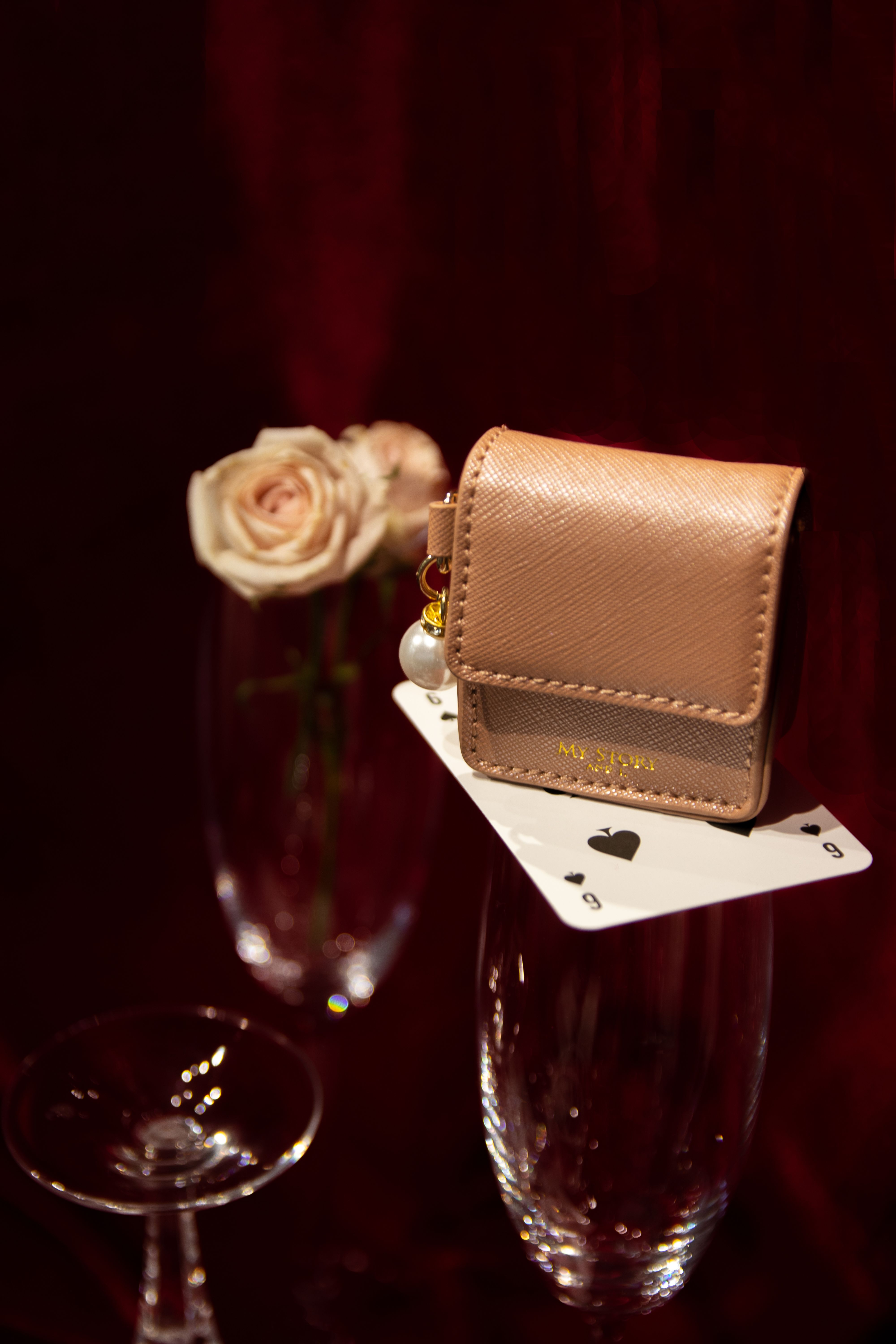 Photo shoot of a bag, playing card and flower - part of the My Story and I collection.
