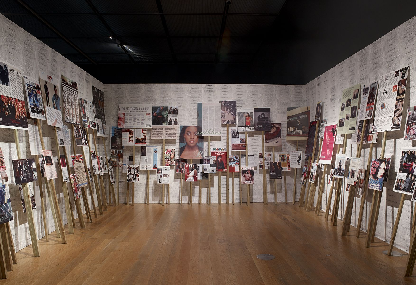 3 walls of an indoor installation of placards with images mounted on sticks of different heights