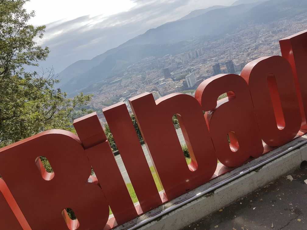 A sign made of large red letters making the word Bilbao, shot from high overlooking Bilbao city