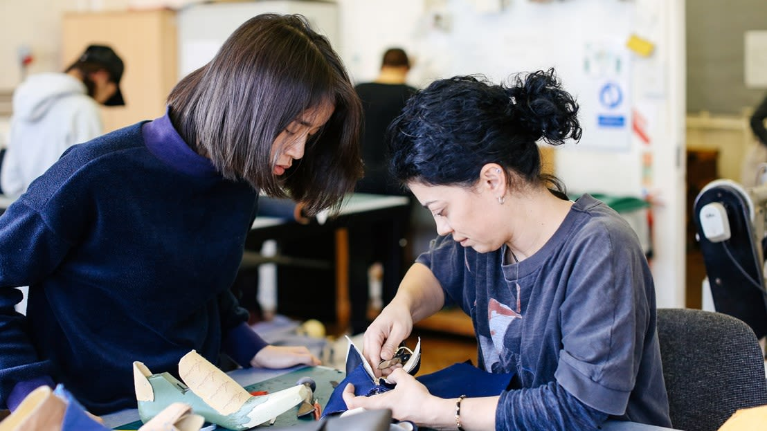 A female lecturer and student working together on a piece of making