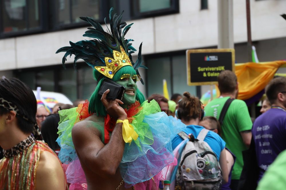 A person in fancy dress, on their phone, in the middle of a crowd at a Pride parade.