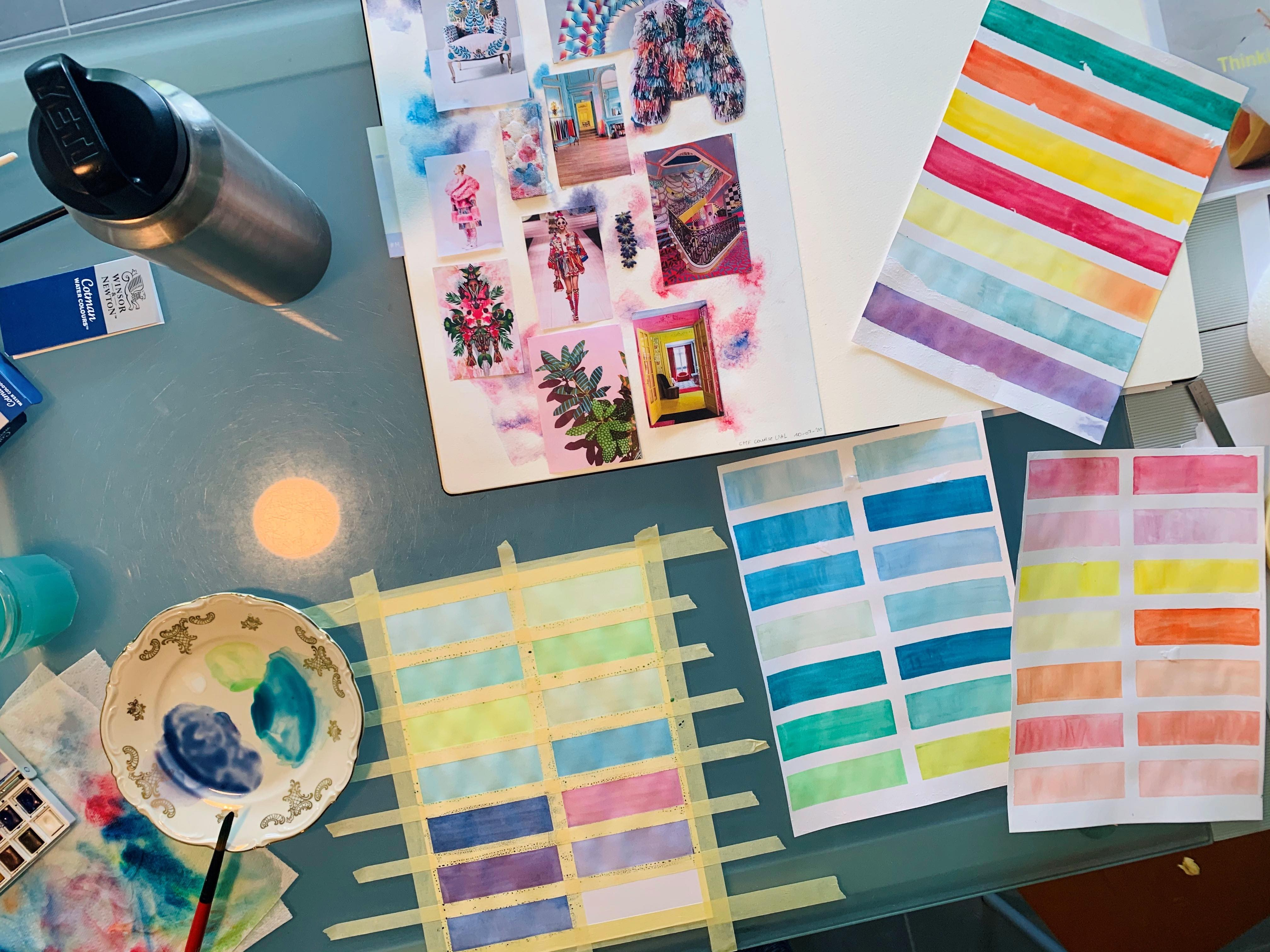 A photo of a desk with paint swatches and sketchbooks