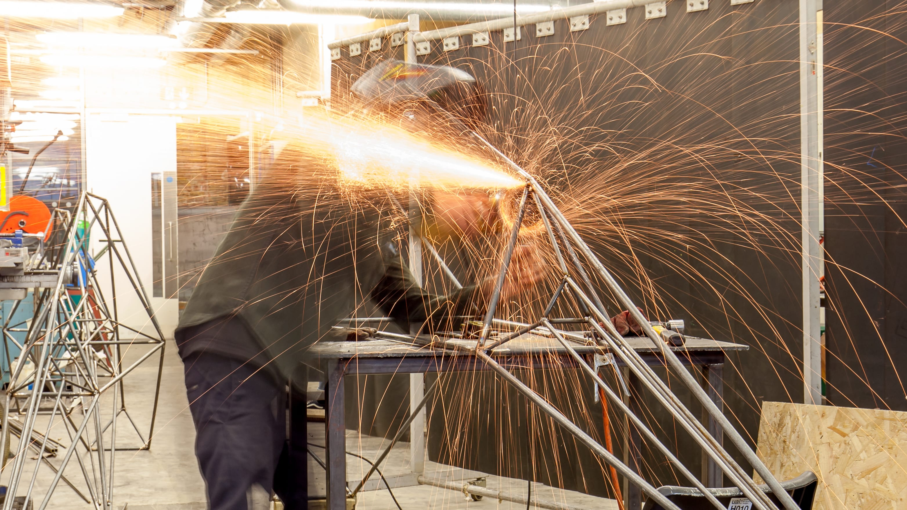 A student welding in the metal workshop