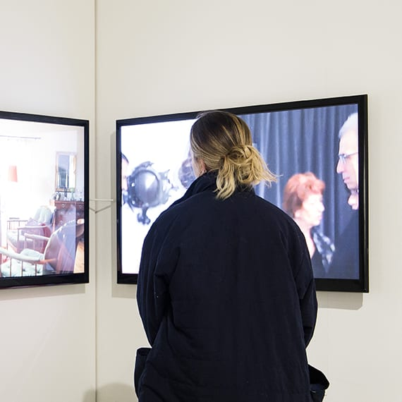 A figure looking at two video screens in a gallery