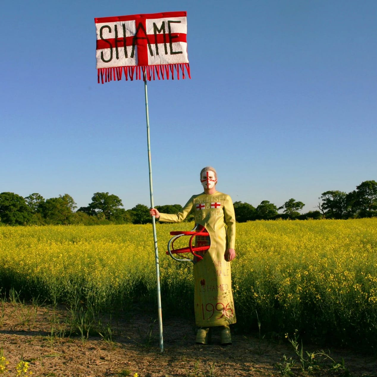 A person stood in a field holding an English flag