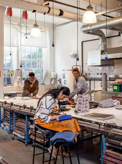 Students in Lime Grove's print workshop with print works on high table tops