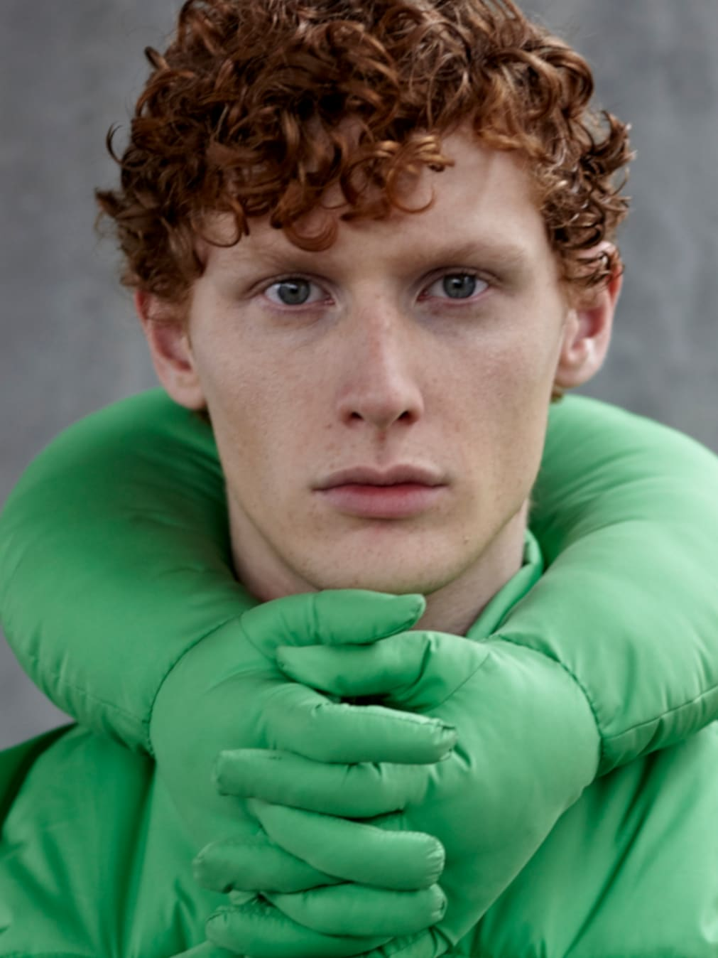 Red-haired model in turquoise padded coat with interlaced fingers