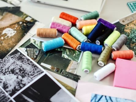 Photo of scattered threads and photographs on a desk