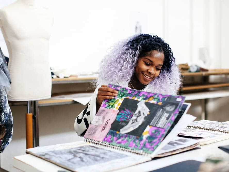 Female student with purple hair flicking through her sketchbook