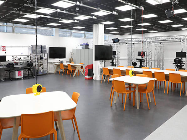 empty workshop space with chairs, tables, tv screen's vr booths and coding area