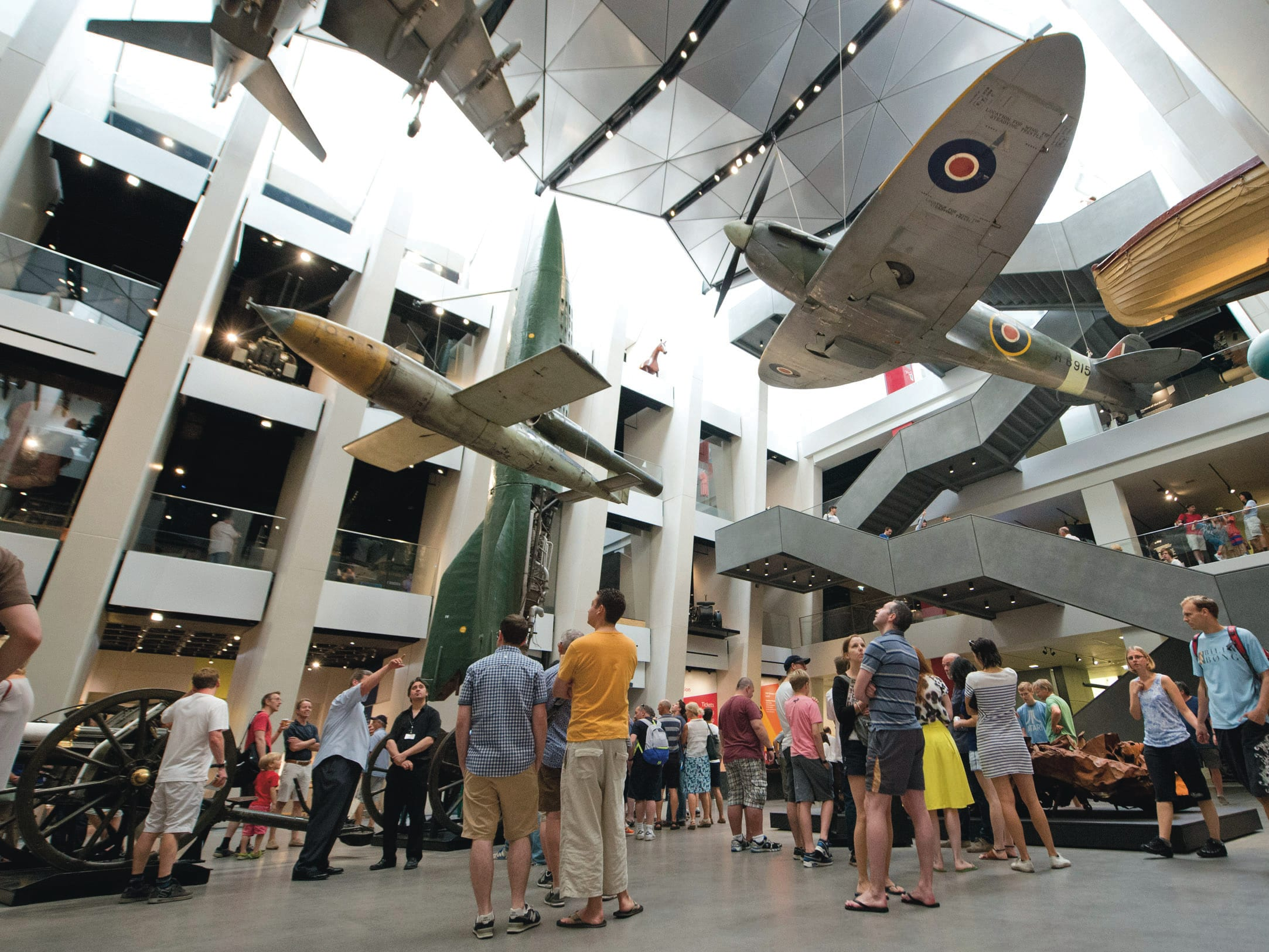 People standing underneath hanging aeroplanes in a museum.