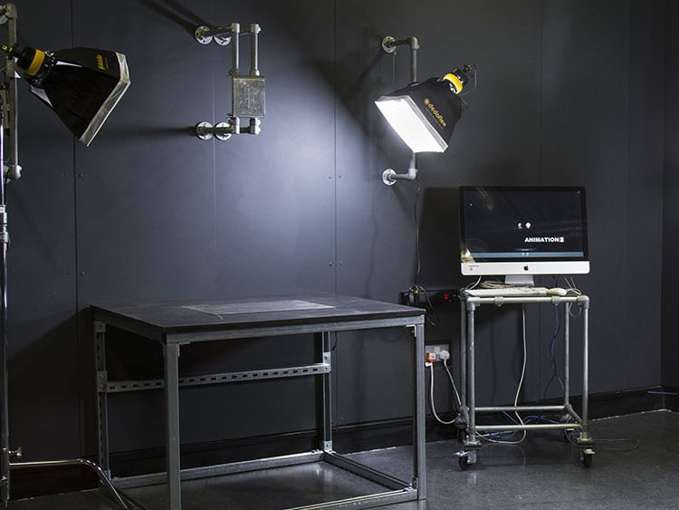 A dark room with an iMac and lighting