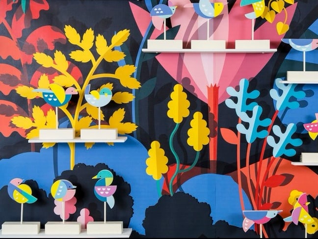Miniature bird statues in front of a very colourful painted background of plants and trees